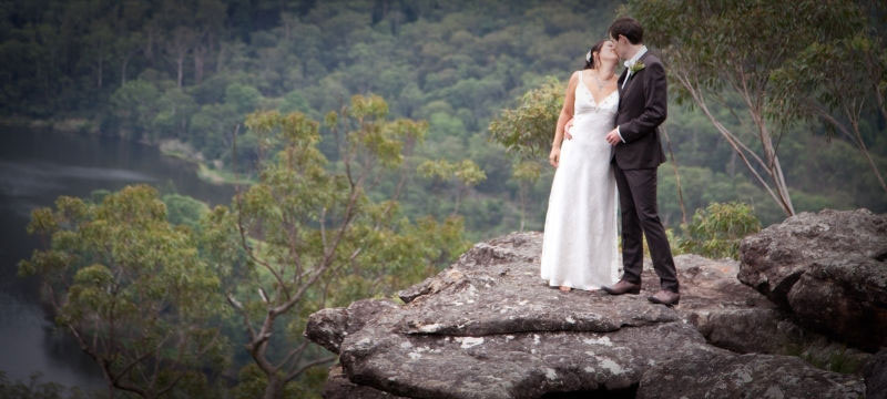 Bride and groom standing on rocks overlooking valley and river at Kangaroo Valley Bush Retreat wedding venue at Kangaroo Valley in NSW.