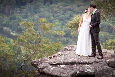 Bride and Groom photo at Kangaroo Valley Bush Retreat wedding venue standing on cliff overlooking valley.