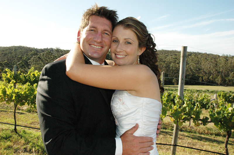 Bride and Groom embracing in front of grape vines at Mimosa Wines wedding venue on the South Coast of NSW.