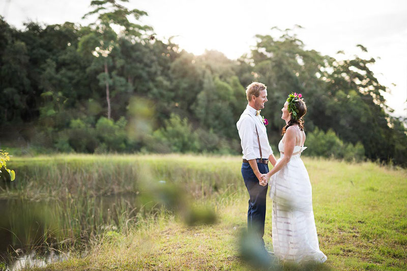 Bride and Groom holding hands and looking at each other at The Barn At Clyde Ridge Wedding Venue