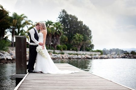 Bride and groom embracing on the wharf at the Coachhouse Marina Resort.