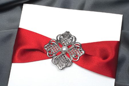 Handmade invitation with red ribbon and pearl embellishment by Instyle Invitations south coast.