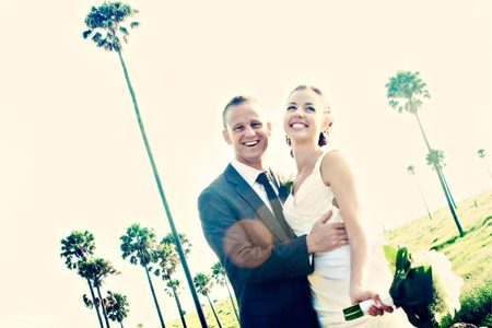 Happy bride and groom with palm tree background and white rose bouquet wedding photo by Peter Izzard Photography