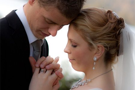 Wedding photo of bride and groom lookin at wedding ring by Photique Photography