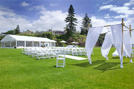 Wedding ceremony setting with rows of white chairs on green lawn with arbour and wedding reception marque.