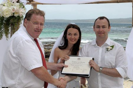 Bride and Groom with wedding celebrant Paul Meagher at beach wedding ceremony.