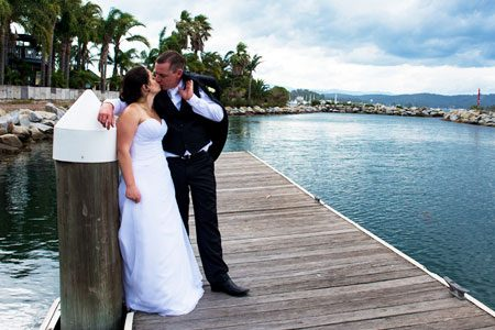 Bride and Groom kissing on the pier. Wedding photography by A Shot In The Dark Photograhy - Batemans Bay NSW