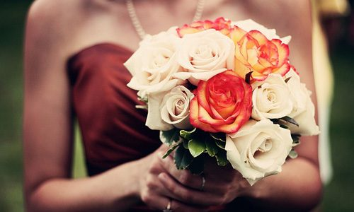 Bride with burgundy dress and autumn themed bridal bouquet.