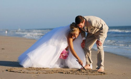 Bride and groom on beach with pink bridal bouquet bending down and drawing a heart in the sand.