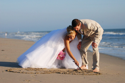 Bride and groom on beach with pink bridal bouquet bending down and drawing a love heart in the sand.