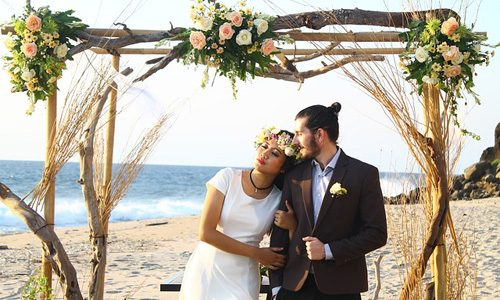 Wedding with beach wedding theme. Bride and groom on the beach under a branch arbour with roses.