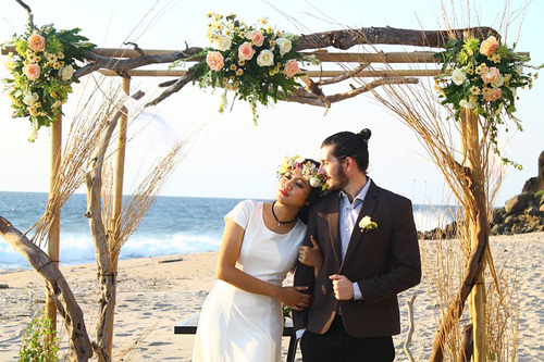 Beach theme wedding photo of bride and groom on the beach under a branch arbour with roses.