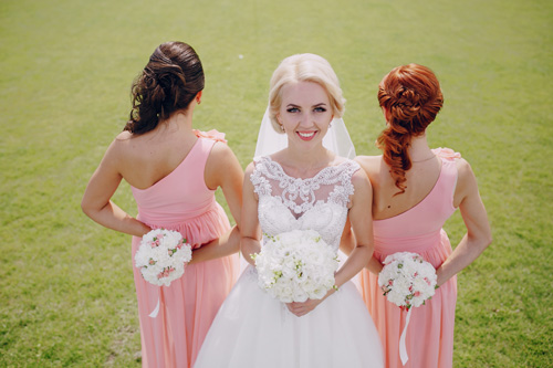 Bride with her two bridesmaids in pink dresses with flower bouquets. Things to consider when choosing bridesmaids.