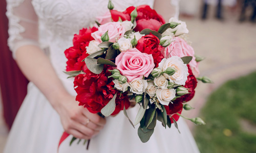 Bridal bouquet with red peonies, pink and champagne roses. Choosing wedding flowers.