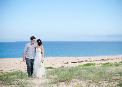 Culburra Beach. Wedding couple looking at each other standing on the beach amongst the sand dunes and grass. Wedding photography by Nora Devai.