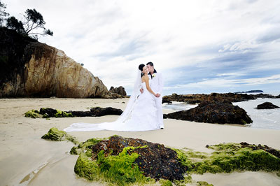 Denhams Beach, Batemans Bay. Wedding couple embracing on the sand among rocks on the beach. Wedding photography by Nora Devai.