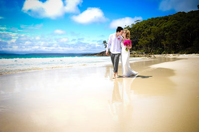 Greenfields Beach, Jervis Bay. Bride and groom walking along wet sand and kissing with bright pink bridal bouquet. Wedding photography by Nora Devai.