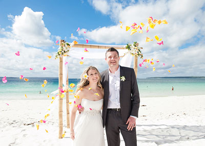 Hyams Beach Jervis Bay. Smiling wedding couple standing in front of an arbour on the beach with flower petals flying through the air. Wedding photography by Nora Devai.