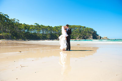 Lilli Pilli Beach Batemans Bay. Bride and groom embracing with their feet in the wet sand on the beach. Wedding photography by Nora Devai.