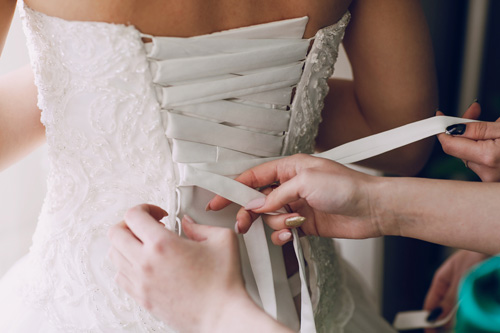 Helping the bride lace up her dress. One of the duties on the maid of honor duty list.