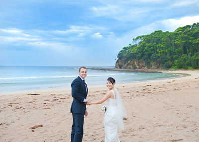 McKenzies Beach Malula Bay. Bride and groom holding hands on the beach and posing for the camera. Wedding photography by Nora Devai.