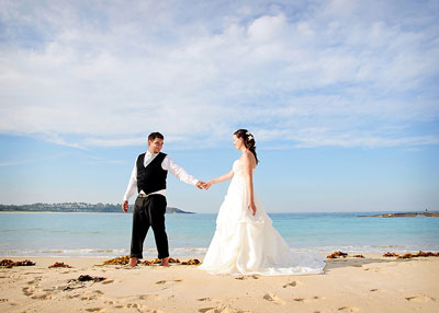 Mollymook Beach. Bride and groom holding hands and looking at each other standing on the sand at the beach. Wedding photography by Nora Devai.