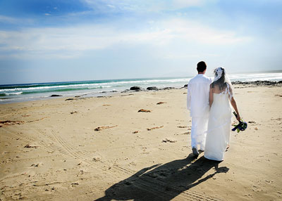 Seven Mile Beach Gerroa. Bride and groom walking on the sand overlooking the beach. Wedding photography by Norai Devai.
