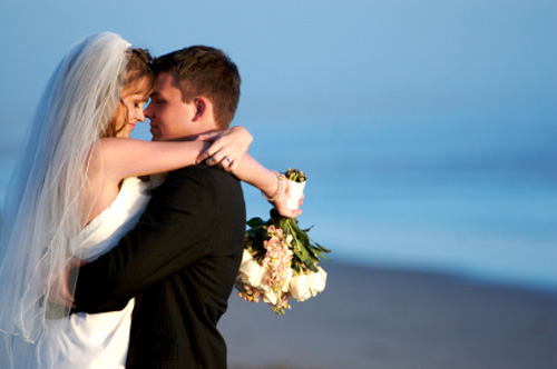 Wedding couple embracing on the beach.