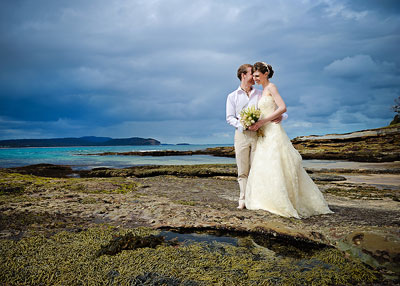 South Durras Murramarrang. Bride and groom on the rocks at the beach with bouquet. Wedding photography by Nora Devai