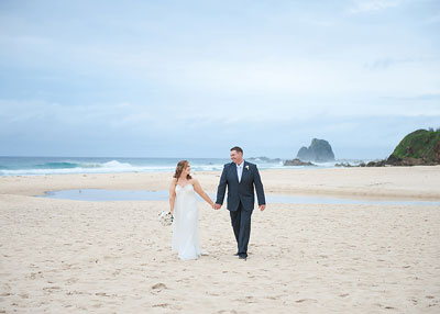 Surf Beach Narooma. Bride and groom holding hands on the beach at. Wedding photography by Nora Devai.