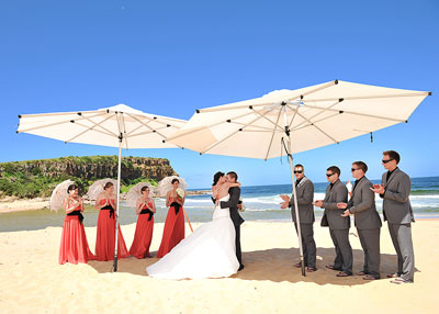 Wedding ceremony under umbrellas at Werri Beach, Gerringong. Wedding photography by Nora Devai.
