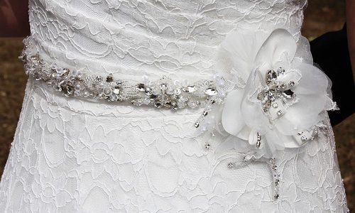 Lacy wedding dress with fabric flower, silver and crystal bead sash.