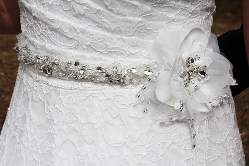Lacy wedding dress with fabric flower, silver and crystal bead sash perfect for a winter wedding theme.