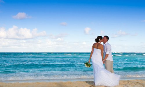 Bride and groom on a sandy beach kissing.